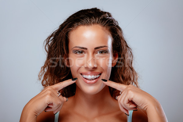 Kijken mijn bretels glimlachend jonge vrouw tonen Stockfoto © MilanMarkovic78