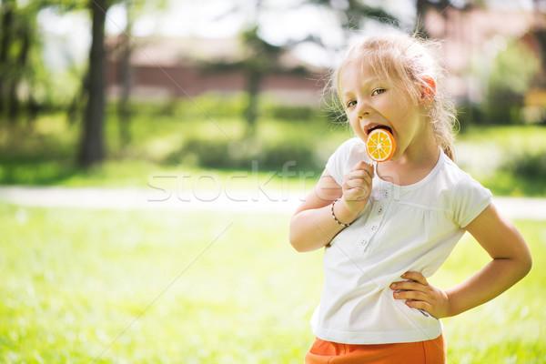 Meisje lolly cute permanente groen gras park Stockfoto © MilanMarkovic78