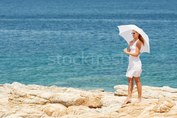 Woman with umbrella Walking on the Beach Stock photo © MilanMarkovic78