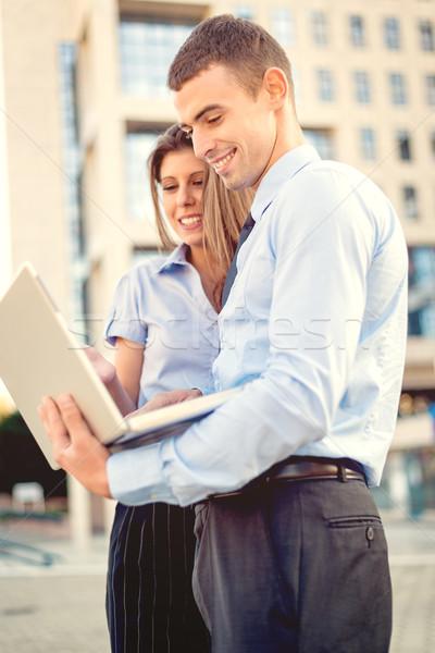 Fiatal üzleti partnerek laptop mosolyog üzletember üzletasszony Stock fotó © MilanMarkovic78