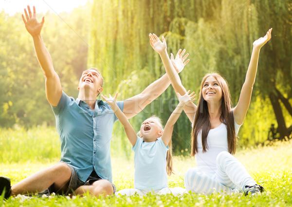 Uśmiechnięty szczęśliwą rodzinę szczęśliwy rodziny posiedzenia trawy Zdjęcia stock © MilanMarkovic78