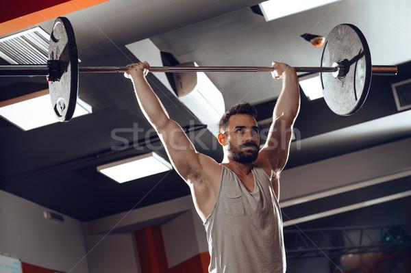Empurrando jovem muscular homem levantamento de peso Foto stock © MilanMarkovic78