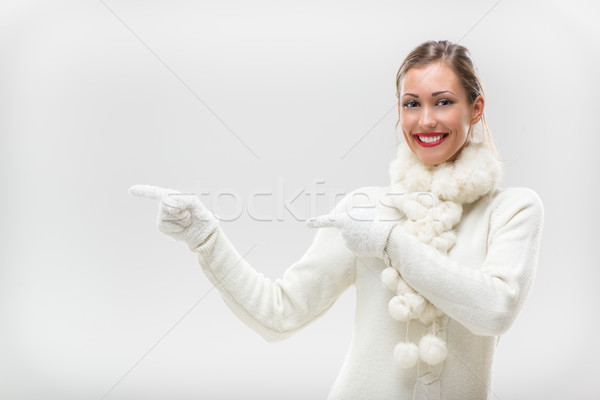Girl In Winter Clothes Pointing Away Stock photo © MilanMarkovic78