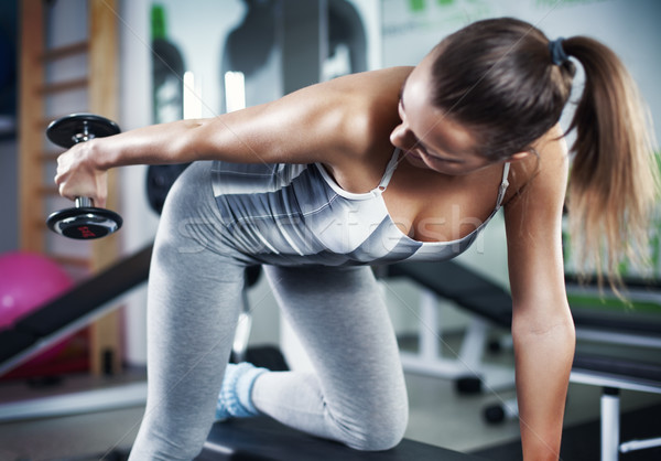 Stock photo: Young woman doing triceps exercise