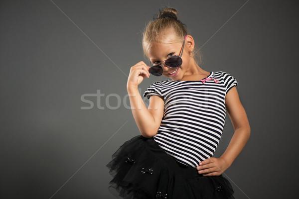 девочку довольно улыбаясь позируют Солнцезащитные очки студию Сток-фото © MilanMarkovic78