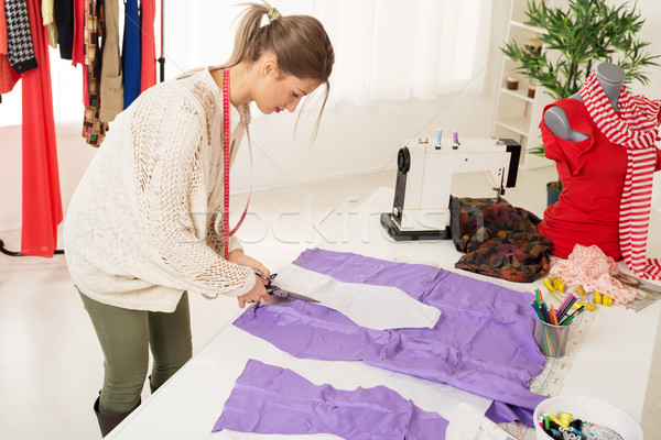 Stock photo: Female Tailor Cutting Material