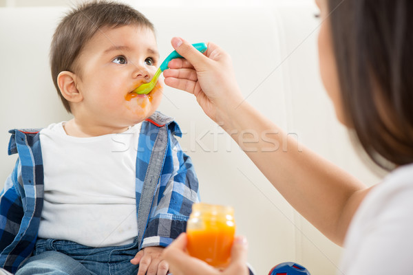 Stock photo: Mother feeding her baby