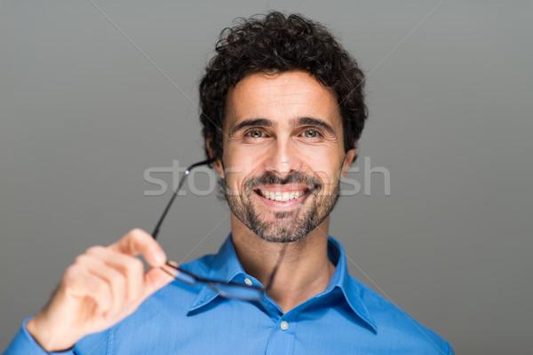 Portrait of a handsome man holding eyeglasses Stock photo © Minervastock