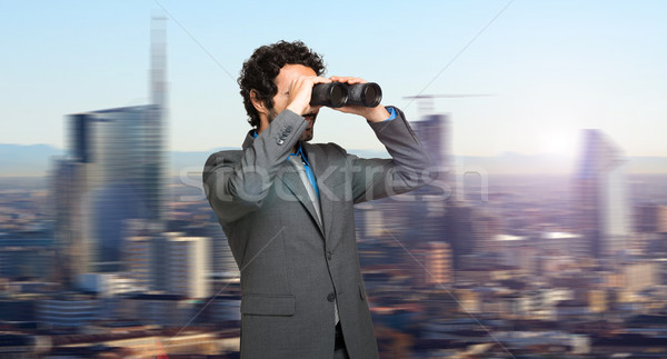 Businessman with binoculars spying on competitors Stock photo © Minervastock