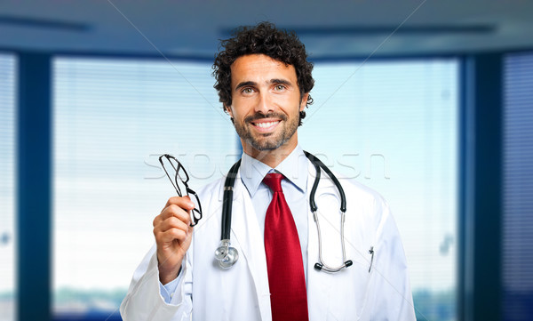 Young doctor giving you a pair of eyeglasses Stock photo © Minervastock