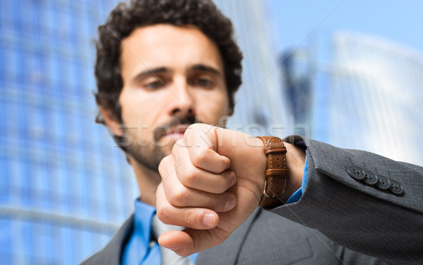 Businessman looking at his watch in front of his office. Focus on the wrist Stock photo © Minervastock