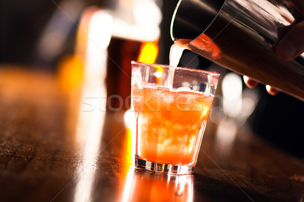 Barman pouring a cocktail into a glass Stock photo © Minervastock