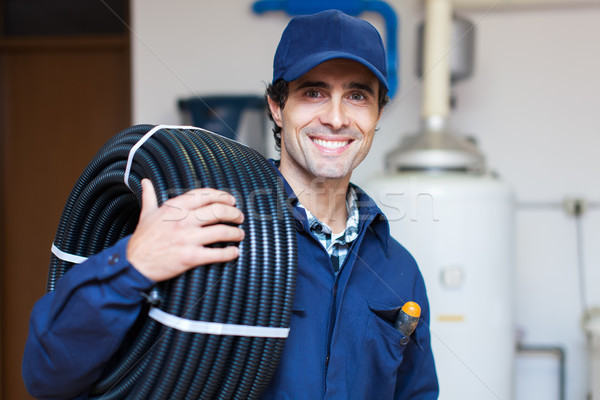 Portrait of a smiling worker carrying corrugated conduit Stock photo © Minervastock