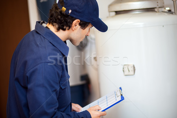 Smiling technician repairing an hot-water heater Stock photo © Minervastock