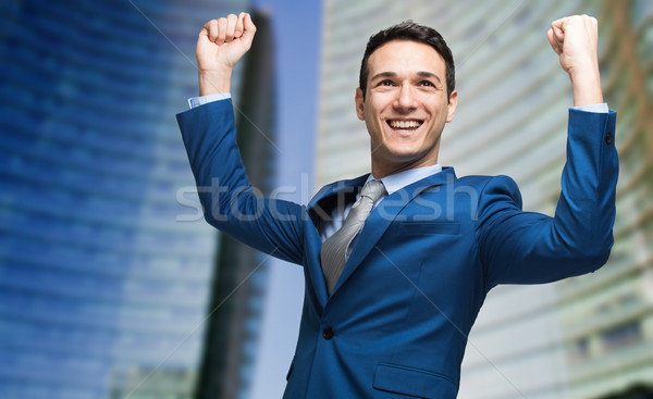 Portrait of a andsome businessman raising arms in sign of victory Stock photo © Minervastock