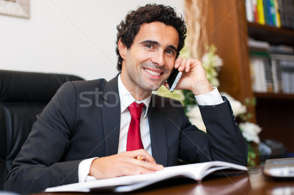 Cheerful man in office answering the phone  Stock photo © Minervastock