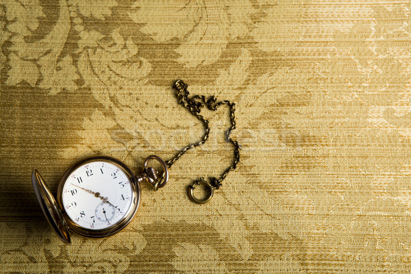 Gold pocket watch on gold cloth Stock photo © mizar_21984