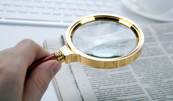 man's hand holds a magnifying glass over a newspaper Stock photo © mizar_21984