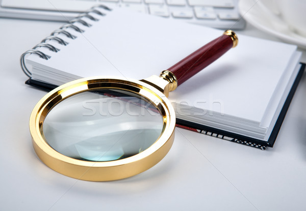 large magnifying glass lies on a notebook on the desktop Stock photo © mizar_21984