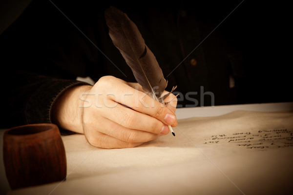 writer holds a fountain pen over writing paper and the writing p Stock photo © mizar_21984
