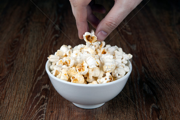 Puchar soli popcorn drewniany stół ludzka ręka Zdjęcia stock © mizar_21984