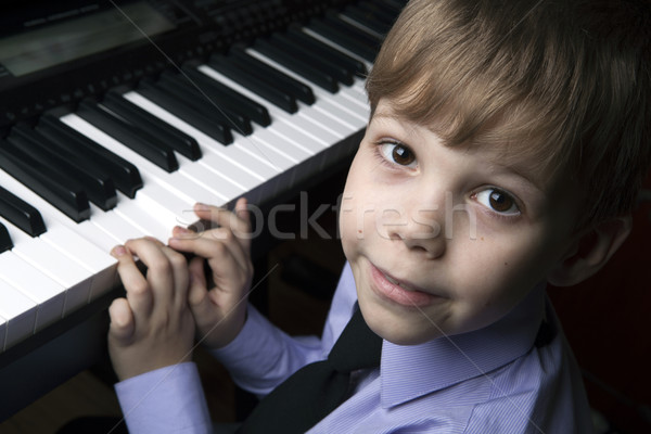 smiling little boy sitting at the piano Stock photo © mizar_21984