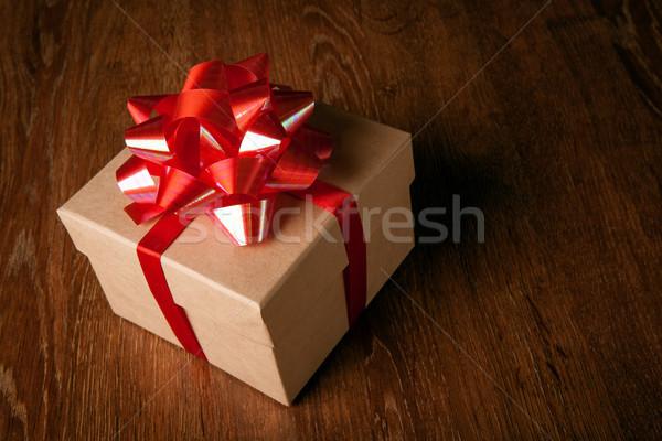 Uno scatola regalo rosso arco tavolo in legno Foto d'archivio © mizar_21984