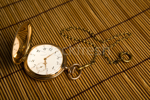 Gold pocket watch on bamboo rugs Stock photo © mizar_21984