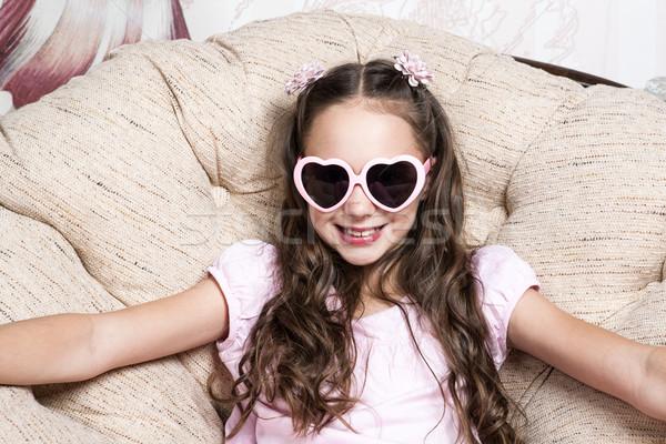 Retrato little girl rosa óculos de sol poltrona sorrir Foto stock © mizar_21984