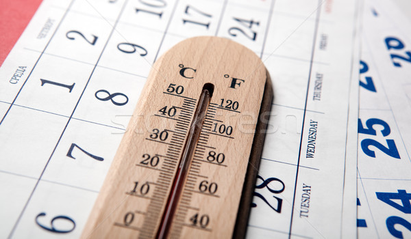 wall thermometer on white table on sheets of the wall calendar Stock photo © mizar_21984