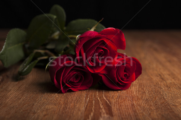 bouquet of roses lying on a wooden table on a black background Stock photo © mizar_21984