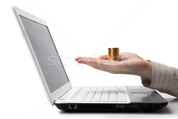 man's hand holding a stack of coins on a laptop Stock photo © mizar_21984