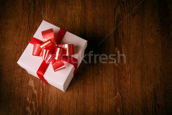 One white festive gift box with a red bow on a wooden table Stock photo © mizar_21984