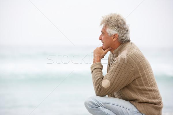 Idős férfi ünnep térdel tél tengerpart Stock fotó © monkey_business