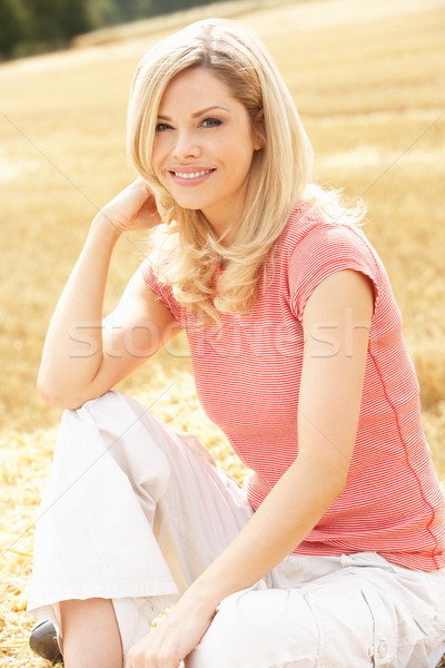 Woman Sitting On Straw Bales In Harvested Field Stock photo © monkey_business