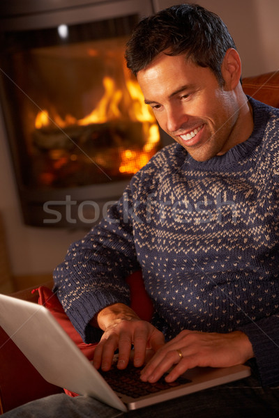 Middle Aged Man Using Laptop Computer By Cosy Log Fire Stock photo © monkey_business