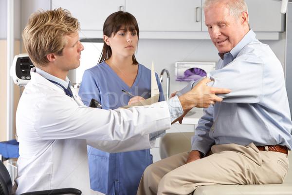 Orvos megvizsgál férfi beteg könyök fájdalom Stock fotó © monkey_business