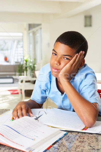 Fed Up Boy Doing Homework In Kitchen Stock photo © monkey_business