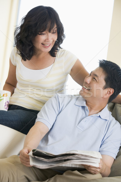 Stock photo: Couple relaxing with a newspaper and smiling