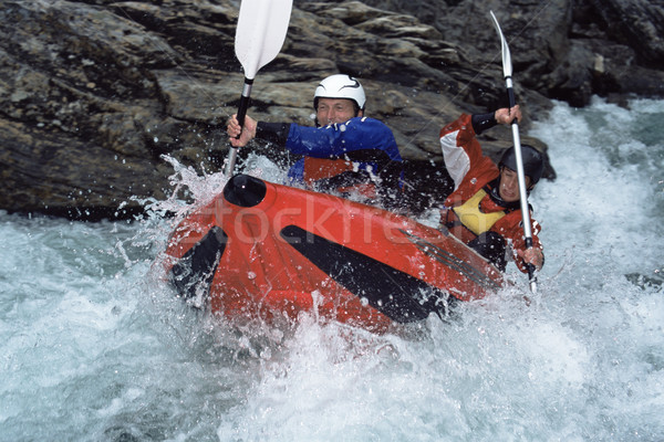 Two people paddling inflatable boat down rapids Stock photo © monkey_business