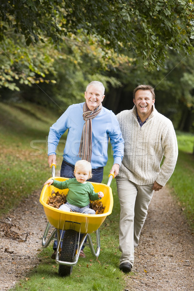 Grandfather with grandson and son pushing wheelbarrow Stock photo © monkey_business