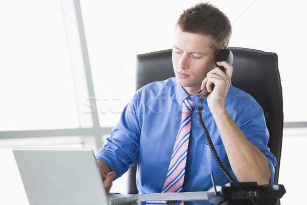 Businessman sitting in office with laptop on telephone Stock photo © monkey_business