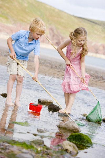 Brother and sister at beach with nets and pail Stock photo © monkey_business