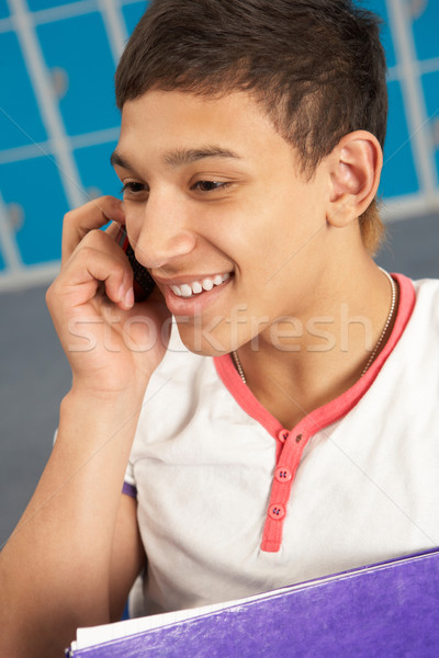 Male Teenage Student Using Mobile Phone By Lockers In School Stock photo © monkey_business