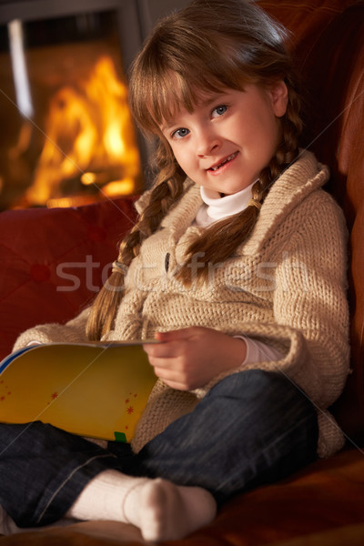 Young Girl Sitting On Sofa And Reading Book By Cosy Log Fire Stock photo © monkey_business