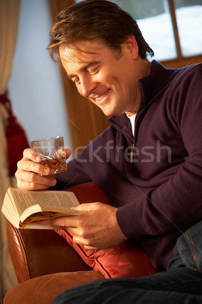 Középkorú férfi megnyugtató könyv ül kanapé iszik Stock fotó © monkey_business