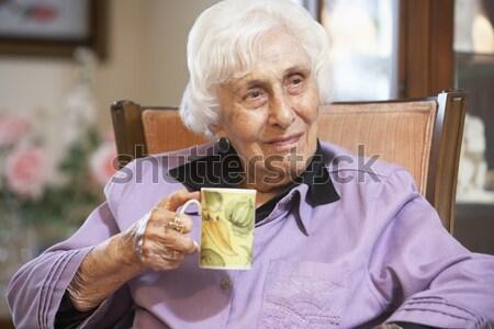 Stock photo: Senior Chinese Man Drinking Tea On Sofa At Home