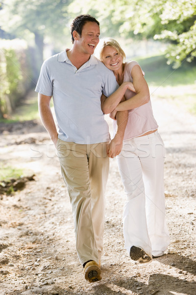 Couple walking outdoors arm in arm smiling Stock photo © monkey_business