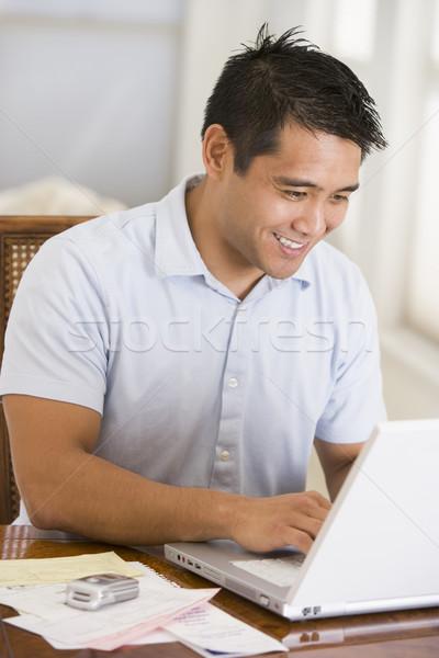 Homem sala de jantar usando laptop sorridente trabalhando retrato Foto stock © monkey_business