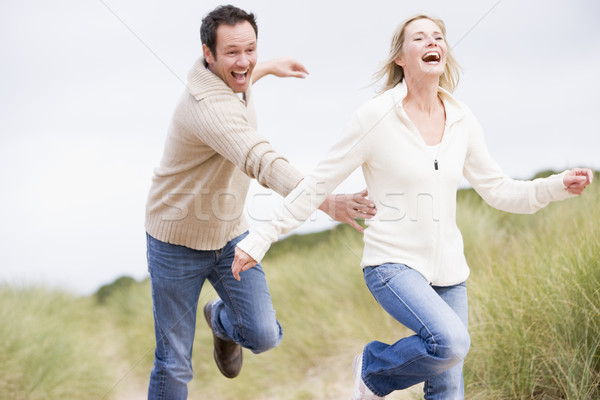Stock photo: Couple running at beach smiling